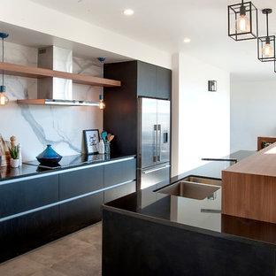 Zweizeilige, Mittelgroße Moderne Wohnküche mit Unterbauwaschbecken, Granit-Arbeitsplatte, Küchengeräten aus Edelstahl, Porzellan-Bodenfliesen, Kücheninsel, flächenbündigen Schrankfronten, schwarzen Schränken, Rückwand aus Stein, Küchenrückwand in Weiß und schwarzer Arbeitsplatte in Christchurch