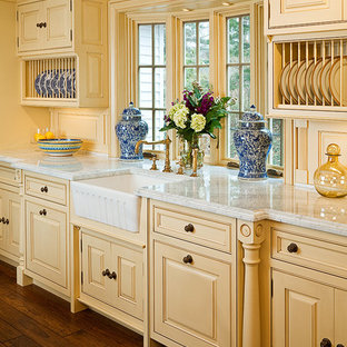 Traditional eat-in kitchen designs - Elegant dark wood floor eat-in kitchen photo in Bridgeport with a farmhouse sink, marble countertops, beaded inset cabinets, yellow cabinets and an island