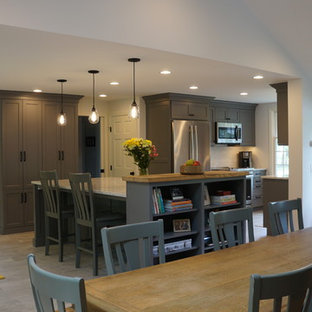 Small country galley open plan kitchen in Boston with a farmhouse sink, shaker cabinets, grey cabinets, quartz benchtops, white splashback, matchstick tile splashback, stainless steel appliances, porcelain floors, with island, grey floor and yellow benchtop.