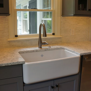 Photo of a small country galley open plan kitchen in Boston with a farmhouse sink, shaker cabinets, grey cabinets, quartz benchtops, white splashback, matchstick tile splashback, stainless steel appliances, porcelain floors, with island, grey floor and yellow benchtop.