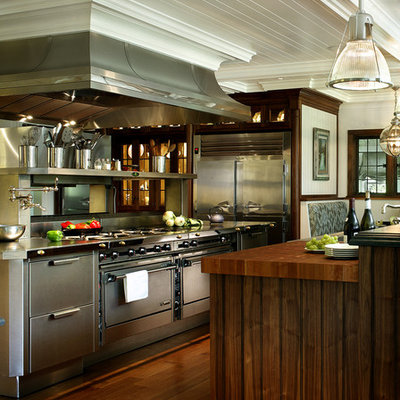 Example of a large transitional dark wood floor eat-in kitchen design in New York with flat-panel cabinets, stainless steel cabinets, wood countertops and stainless steel appliances