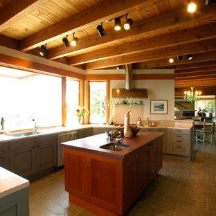 Immagine di una cucina eclettica di medie dimensioni con lavello sottopiano, ante lisce, ante in legno scuro, top in pietra calcarea, paraspruzzi beige, paraspruzzi in lastra di pietra, elettrodomestici in acciaio inossidabile, pavimento con piastrelle in ceramica e isola