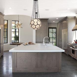 Esempio di un'ampia cucina chic con ante marroni, paraspruzzi a effetto metallico, elettrodomestici in acciaio inossidabile, isola, lavello stile country, ante di vetro, top in marmo, paraspruzzi in marmo, pavimento in pietra calcarea, pavimento nero e top bianco