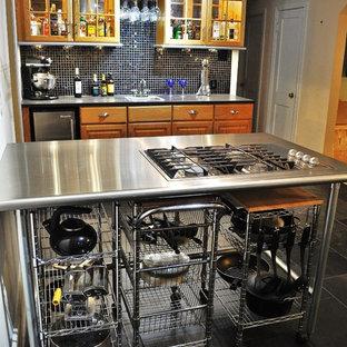 リッチモンドの中サイズのエクレクティックスタイルのおしゃれなキッチン (ドロップインシンク、レイズドパネル扉のキャビネット、中間色木目調キャビネット、ステンレスカウンター、黒いキッチンパネル、ガラスタイルのキッチンパネル、シルバーの調理設備の、スレートの床) の写真