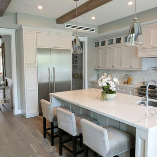 Large modern u-shaped eat-in kitchen in San Francisco with an integrated sink, louvered cabinets, white cabinets, marble benchtops, white splashback, stainless steel appliances, light hardwood floors, with island, grey floor, white benchtop and porcelain splashback.