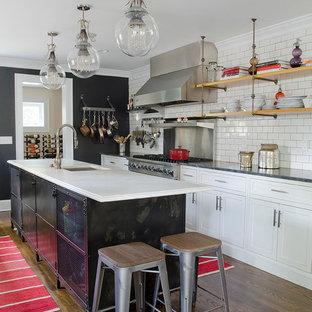 ニューヨークのインダストリアルスタイルのおしゃれなアイランドキッチン (ドロップインシンク、シェーカースタイル扉のキャビネット、白いキャビネット、白いキッチンパネル、サブウェイタイルのキッチンパネル、シルバーの調理設備の、濃色無垢フローリング) の写真