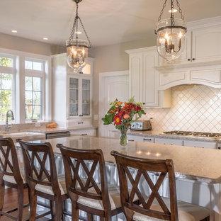 Foto di una cucina classica con lavello stile country, ante con bugna sagomata, ante bianche, paraspruzzi bianco, elettrodomestici in acciaio inossidabile, parquet scuro e isola
