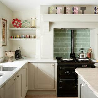 Ispirazione per una cucina di medie dimensioni con lavello da incasso, ante in stile shaker, ante beige, top in superficie solida, elettrodomestici neri, parquet chiaro, isola, pavimento grigio e top giallo