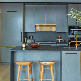 Contemporary kitchen ideas - Trendy l-shaped light wood floor kitchen photo in New York with an undermount sink, flat-panel cabinets, blue cabinets, paneled appliances and a peninsula