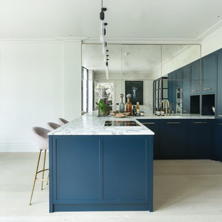 Inspiration for a contemporary u-shaped kitchen/diner in London with a submerged sink, shaker cabinets, blue cabinets, metallic splashback, mirror splashback, stainless steel appliances, light hardwood flooring, a breakfast bar, beige floors and white worktops.