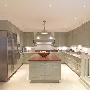 ロンドンの大きいトラディショナルスタイルのおしゃれなアイランドキッチン (アンダーカウンターシンク、レイズドパネル扉のキャビネット、緑のキャビネット、ライムストーンカウンター、白いキッチンパネル、シルバーの調理設備の、ライムストーンの床) の写真