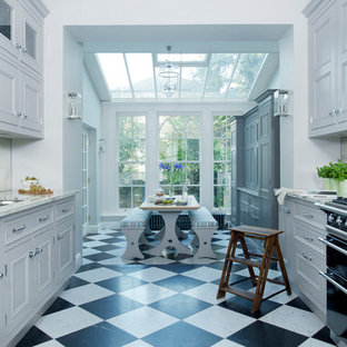 Large classic galley kitchen/diner in London with a submerged sink, beaded cabinets, grey cabinets, granite worktops, mirror splashback, black appliances, marble flooring and no island.