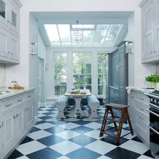 ロンドンの大きいトラディショナルスタイルのおしゃれなキッチン (アンダーカウンターシンク、インセット扉のキャビネット、グレーのキャビネット、御影石カウンター、ミラータイルのキッチンパネル、黒い調理設備、大理石の床、アイランドなし) の写真