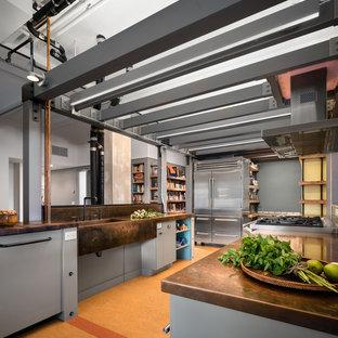 ニューヨークの広いインダストリアルスタイルのおしゃれなキッチン (一体型シンク、フラットパネル扉のキャビネット、グレーのキャビネット、銅製カウンター、シルバーの調理設備、コルクフローリング、アイランドなし、茶色い床) の写真