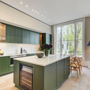 Medium sized classic single-wall kitchen/diner in London with an island, green cabinets, white splashback, marble splashback, stainless steel appliances, light hardwood flooring, beige floors, white worktops and shaker cabinets.