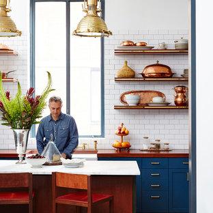 Ejemplo de cocina en L, bohemia, de tamaño medio, abierta, con fregadero sobremueble, armarios estilo shaker, puertas de armario azules, encimera de madera, salpicadero blanco, salpicadero de azulejos tipo metro, suelo de madera oscura y una isla