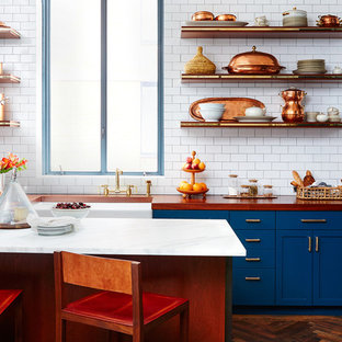 Mid-sized eclectic open concept kitchen ideas - Mid-sized eclectic l-shaped dark wood floor open concept kitchen photo in San Francisco with a farmhouse sink, shaker cabinets, blue cabinets, wood countertops, white backsplash, subway tile backsplash and an island