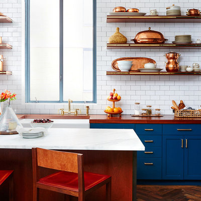 Mid-sized eclectic l-shaped dark wood floor open concept kitchen photo in San Francisco with a farmhouse sink, shaker cabinets, blue cabinets, wood countertops, white backsplash, subway tile backsplash and an island