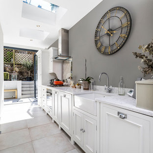 Small traditional single-wall kitchen in London with white cabinets, marble worktops, cement flooring, no island, grey floors, a belfast sink, recessed-panel cabinets and mirror splashback.