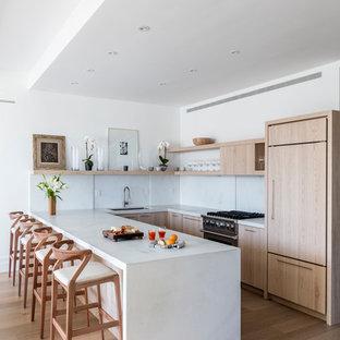 Offene, Zweizeilige Moderne Küche mit Unterbauwaschbecken, flächenbündigen Schrankfronten, hellen Holzschränken, Küchenrückwand in Weiß, Küchengeräten aus Edelstahl, hellem Holzboden, Halbinsel und beigem Boden in New York