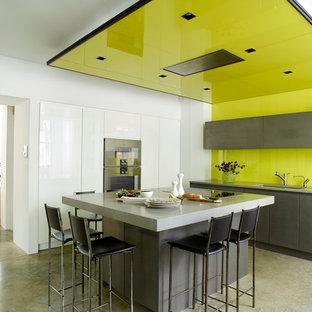 ロンドンの中サイズのコンテンポラリースタイルのおしゃれなキッチン (フラットパネル扉のキャビネット、グレーのキャビネット、緑のキッチンパネル、ガラス板のキッチンパネル、シルバーの調理設備の、コンクリートの床、ドロップインシンク、人工大理石カウンター、グレーの床、グレーのキッチンカウンター) の写真