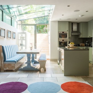 Design ideas for a medium sized classic l-shaped kitchen/diner in London with recessed-panel cabinets, green cabinets, stainless steel appliances, an island, grey floors and black worktops.