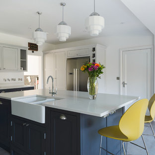 Inspiration for a medium sized classic u-shaped kitchen/diner in Gloucestershire with shaker cabinets, ceramic flooring, an island, blue cabinets, white splashback, stainless steel appliances, a belfast sink and blue floors.