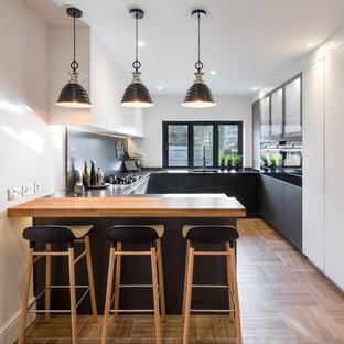 Modelo de cocina en U, contemporánea, de tamaño medio, con puertas de armario grises, encimera de cuarcita, salpicadero verde, electrodomésticos negros, suelo de baldosas de porcelana, península, suelo marrón y armarios con paneles lisos