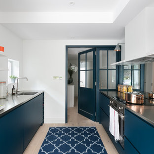 Photo of a contemporary kitchen in London with an integrated sink, flat-panel cabinets, blue cabinets, stainless steel benchtops, light hardwood floors and beige floor.
