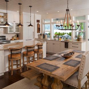 Ejemplo de cocina comedor en L, marinera, con armarios estilo shaker, puertas de armario blancas, salpicadero blanco, salpicadero de azulejos tipo metro, suelo de madera oscura y una isla