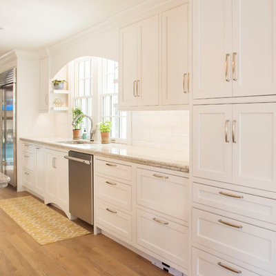 Example of a large classic galley light wood floor open concept kitchen design in Other with an undermount sink, beaded inset cabinets, white cabinets, quartzite countertops, white backsplash, subway tile backsplash, stainless steel appliances and a peninsula