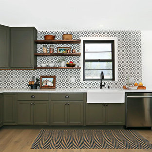 Mediterranean kitchen ideas - Inspiration for a mediterranean l-shaped medium tone wood floor kitchen remodel in Los Angeles with a farmhouse sink, recessed-panel cabinets, green cabinets, multicolored backsplash, stainless steel appliances, no island and cement tile backsplash