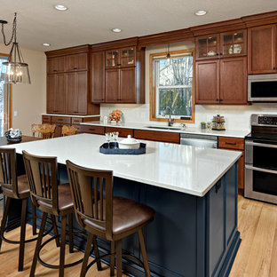 Large traditional eat-in kitchen remodeling - Large elegant l-shaped light wood floor and beige floor eat-in kitchen photo in Minneapolis with an undermount sink, dark wood cabinets, quartz countertops, white backsplash, ceramic backsplash, stainless steel appliances, white countertops, an island and recessed-panel cabinets