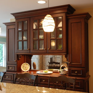Example of a classic u-shaped eat-in kitchen design in Chicago with an undermount sink, flat-panel cabinets, dark wood cabinets, granite countertops, beige backsplash, stone tile backsplash and paneled appliances