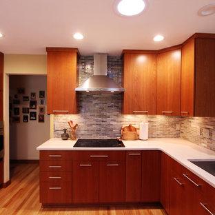 Exempel på ett litet modernt kök, med en undermonterad diskho, släta luckor, skåp i mellenmörkt trä, bänkskiva i kvarts, flerfärgad stänkskydd, stänkskydd i glaskakel, rostfria vitvaror, ljust trägolv och en halv köksö