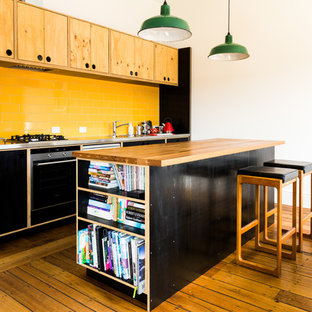 This is an example of a contemporary galley kitchen in Hobart with a drop-in sink, flat-panel cabinets, black cabinets, yellow splashback, subway tile splashback, stainless steel appliances, medium hardwood floors and with island.