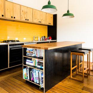 Zweizeilige Moderne Küche mit Einbauwaschbecken, flächenbündigen Schrankfronten, schwarzen Schränken, Küchenrückwand in Gelb, Rückwand aus Metrofliesen, Küchengeräten aus Edelstahl, braunem Holzboden und Kücheninsel in Hobart