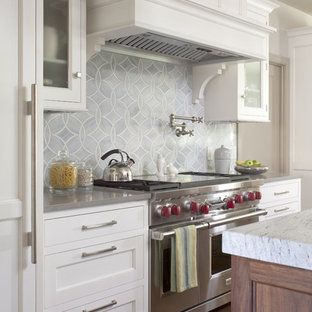 Inspiration for a transitional kitchen remodel in Denver with stainless steel appliances, recessed-panel cabinets, white cabinets, blue backsplash and quartz countertops