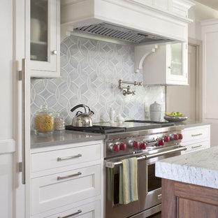 Esempio di una cucina classica con elettrodomestici in acciaio inossidabile, ante con riquadro incassato, ante bianche, paraspruzzi blu e top in quarzo composito