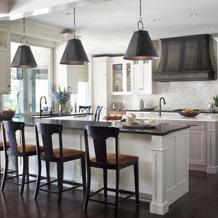 Imagen de cocina comedor en U, clásica renovada, grande, con armarios con paneles empotrados, puertas de armario blancas, encimera de granito, salpicadero blanco, salpicadero de azulejos de piedra, suelo de madera oscura y una isla
