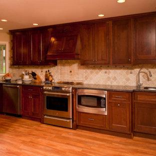 Foto på ett stort vintage kök, med en undermonterad diskho, luckor med profilerade fronter, skåp i mörkt trä, granitbänkskiva, grått stänkskydd, stänkskydd i stenkakel, rostfria vitvaror, mellanmörkt trägolv och brunt golv