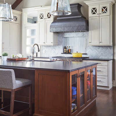 Huge elegant l-shaped dark wood floor and brown floor open concept kitchen photo in Chicago with a farmhouse sink, shaker cabinets, white cabinets, granite countertops, gray backsplash, stone tile backsplash, stainless steel appliances, an island and black countertops