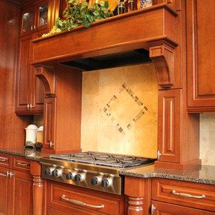 Große Klassische Küche in U-Form mit Triple-Waschtisch, profilierten Schrankfronten, braunen Schränken, Quarzwerkstein-Arbeitsplatte, Küchenrückwand in Beige, Rückwand aus Porzellanfliesen, Küchengeräten aus Edelstahl, Porzellan-Bodenfliesen und Kücheninsel in Cleveland