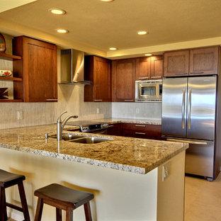 ハワイの中サイズのトロピカルスタイルのおしゃれなキッチン (ダブルシンク、シェーカースタイル扉のキャビネット、中間色木目調キャビネット、御影石カウンター、ベージュキッチンパネル、石タイルのキッチンパネル、シルバーの調理設備、磁器タイルの床、アイランドなし) の写真