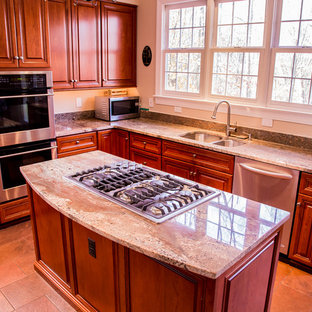 Medium sized rustic l-shaped kitchen/diner in Baltimore with a double-bowl sink, raised-panel cabinets, medium wood cabinets, granite worktops, stainless steel appliances, ceramic flooring, an island and beige splashback.