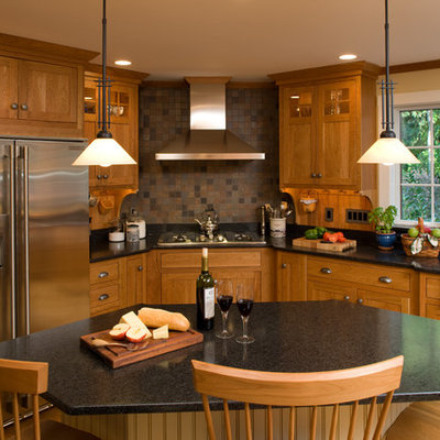 Example of an arts and crafts l-shaped kitchen design in Boston with shaker cabinets, medium tone wood cabinets, granite countertops, brown backsplash, stainless steel appliances and slate backsplash