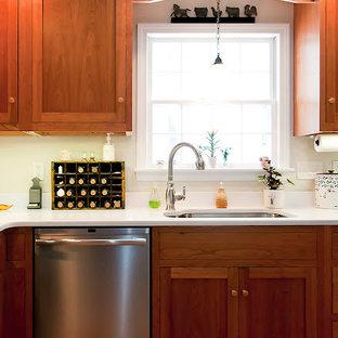 ボストンの大きいトラディショナルスタイルのおしゃれなキッチン (シェーカースタイル扉のキャビネット、濃色木目調キャビネット、人工大理石カウンター、シルバーの調理設備の、アンダーカウンターシンク、テラコッタタイルの床、赤い床) の写真