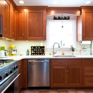 Example of a large classic l-shaped terra-cotta tile and red floor eat-in kitchen design in Boston with an undermount sink, shaker cabinets, dark wood cabinets, solid surface countertops, stainless steel appliances and an island