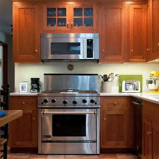 ボストンの広いトラディショナルスタイルのおしゃれなキッチン (アンダーカウンターシンク、シェーカースタイル扉のキャビネット、濃色木目調キャビネット、人工大理石カウンター、シルバーの調理設備、テラコッタタイルの床、赤い床) の写真