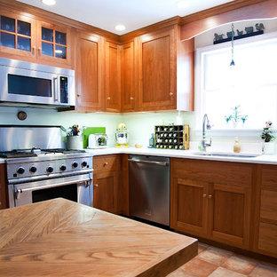 ボストンの大きいトラディショナルスタイルのおしゃれなキッチン (アンダーカウンターシンク、シェーカースタイル扉のキャビネット、濃色木目調キャビネット、人工大理石カウンター、シルバーの調理設備、テラコッタタイルの床、赤い床) の写真